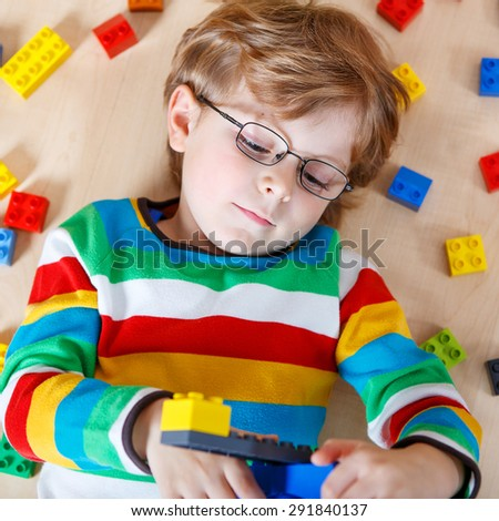 Little blond child playing with lots of colorful plastic blocks indoor. Kid boy wearing colorful shirt and having fun with building and creating. - stock photo
