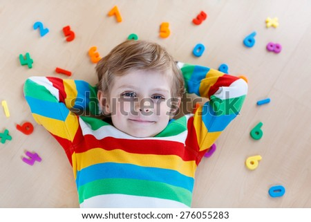 Little blond child playing with lots of colorful plastic digits or numbers, indoor. Kid boy wearing colorful shirt and having fun with learning math - stock photo