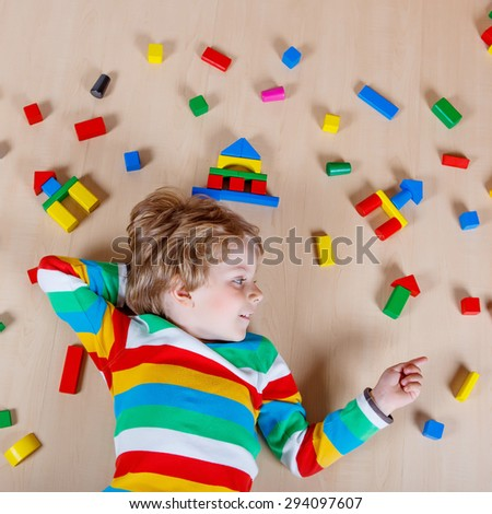 Little blond child playing with lots of colorful wooden blocks indoor. Active kid boy wearing colorful shirt and having fun with building and creating. - stock photo
