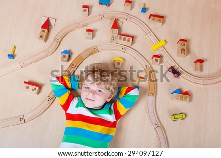 Little blond child playing wooden railroad indoor. Active kid boy wearing colorful shirt and having fun with building and creating. - stock photo