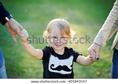 Little blond curly-haired boy smiling and holding hands with mom and dad. - stock photo
