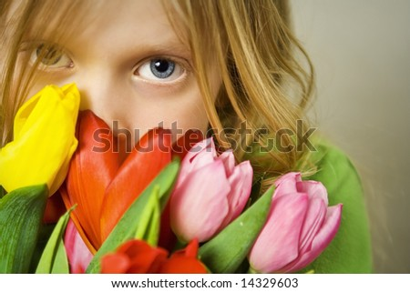 Little blond girl and bunch of colorful tulips - stock photo