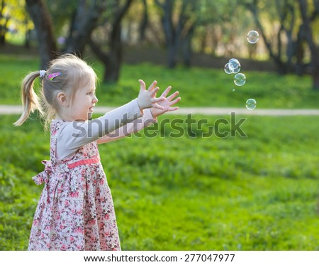 Little blond girl catching soap bubbles, selective focus and space for text - stock photo