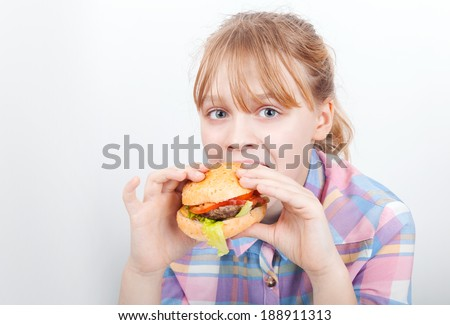 Little blond girl eats hamburger above white wall - stock photo