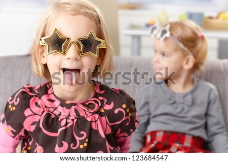 Little blond girl having fun at home, sticking tongue, wearing funny star shaped glasses, little sister in the background. - stock photo