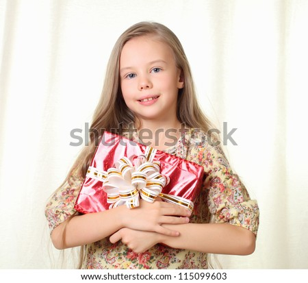 Little blond girl holding a red glamorous gift and smiling - stock photo