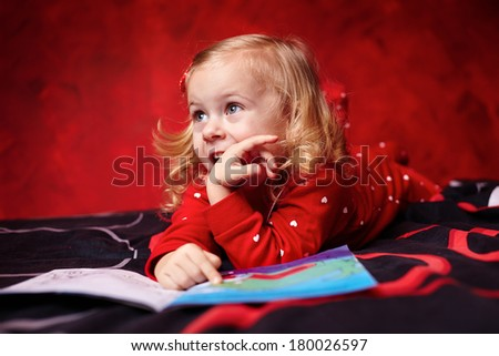 Little blond girl in pajamas reading a cartoon book on the bed before sleeping - stock photo