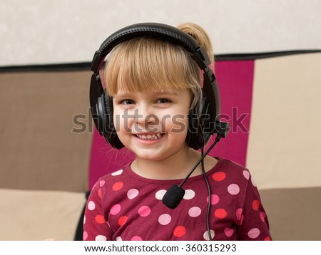 Little blond girl in the headphones with microphone is smiling. Close up - stock photo