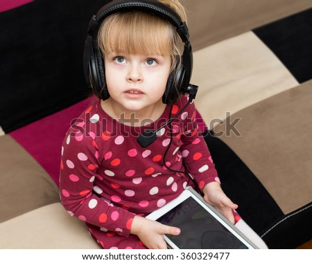 Little blond girl in the headphones with the tablet is looking up. Serious face - stock photo