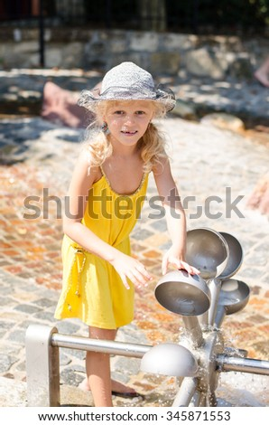 little blond girl playing with water attraction  - stock photo