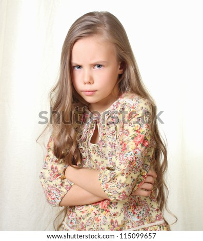 Little blond girl posing with crossed hands on her breast - stock photo
