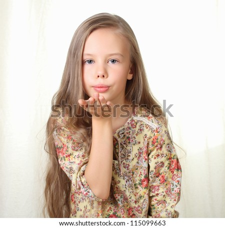 Little blond girl sends air kiss and blowing - stock photo