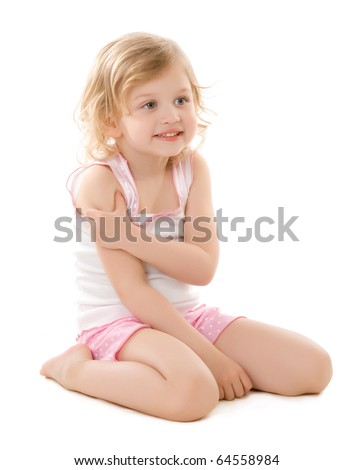little blond girl wearing a pajamas sitting on white background - stock photo