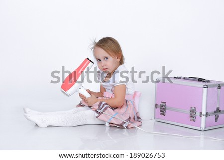 Little blond girl with a hairdryer sitting near a makeup beauty case in a pink and white dress isolated on white in studio - stock photo