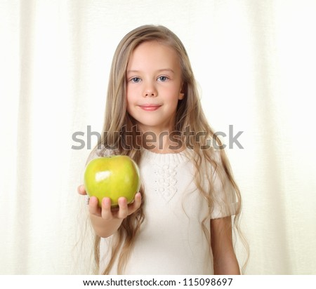 Little blond girl with apple shows in to camera - stock photo
