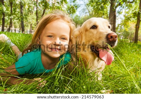 Little blond girl with her retriever dog - stock photo