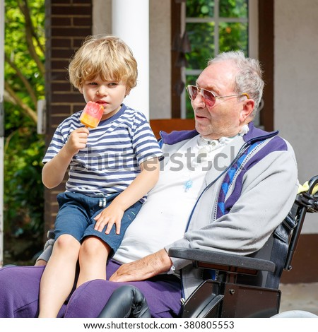 Little blond kid boy and grandfather on wheelchair eating together ice cream in summer. - stock photo