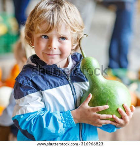 Little blond kid boy holding green pumpkin on halloween or thanksgiving harvest festival or patch, outdoors - stock photo