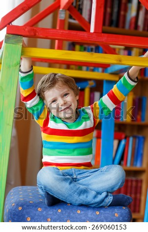Little blond kid boy playing in selfmade wooden colorful house. child having fun indoors. - stock photo