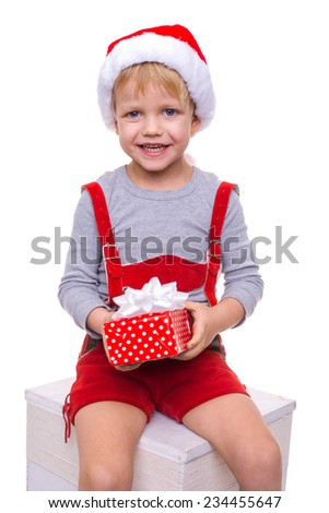Little blond kid in red costume of dwarf holding gift box with ribbon. Christmas. Studio portrait isolated over white background   - stock photo