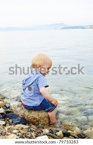 Little blond one year old boy sitting on a rock with his feet in the sea water on a warm summer evening - stock photo