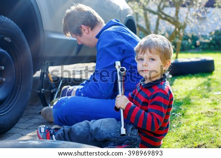 Little blond toddler boy and his father changing wheels on car with pneumatic wrench. Man in uniform teaching his son working with tools. - stock photo