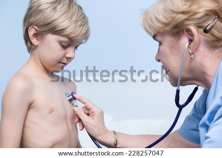 Little blonde boy having examination in hospital - stock photo