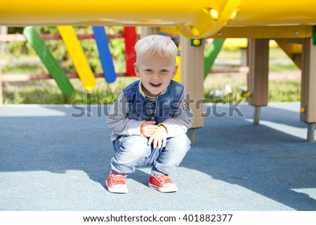 Little blonde boy playing on the playground, outdoors summer - stock photo