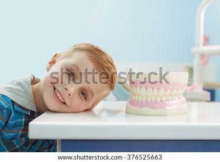 little blonde boy smiling and looking at hte camera near the jaw in dental clinic. copy space - stock photo