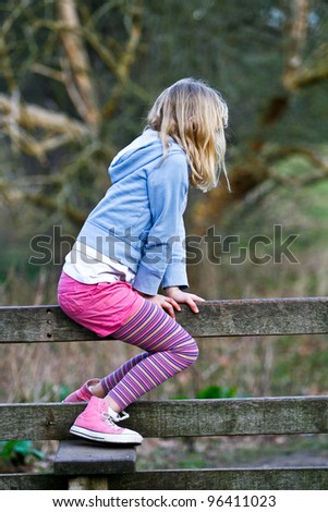 little blonde caucasian girl climbing over a wooden style and looking for adventure - stock photo