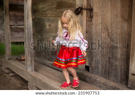little blonde girl in ukrainian national costume are going for a walk - stock photo