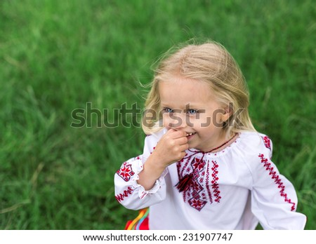 little blonde girl in ukrainian national costume smiling - close up portrait - stock photo