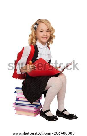 little blonde girl sitting on the books holding textbook with red bag pack over white background - stock photo