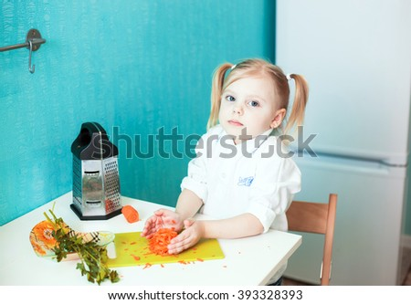 little blonde girl with pigtails four years preparing dinner, t grated carrots, bright colors - stock photo