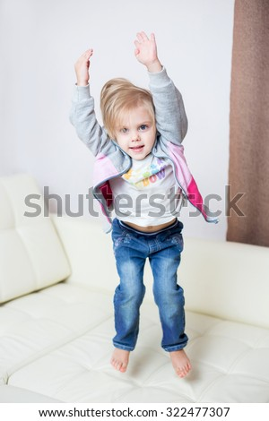 little blonde nice smiling girl three years, jumping on a white leather sofa with bare feet - stock photo