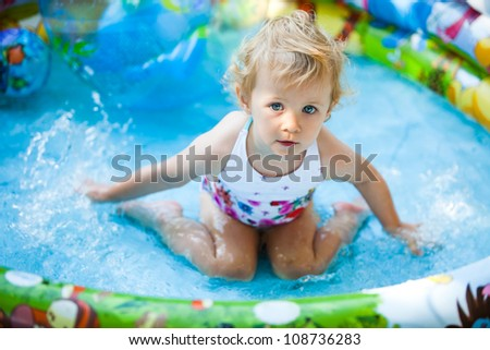 Little blondie girl in the swimming pool - stock photo