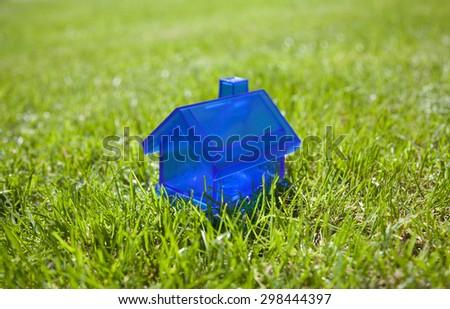Little blue house on green grass  - stock photo