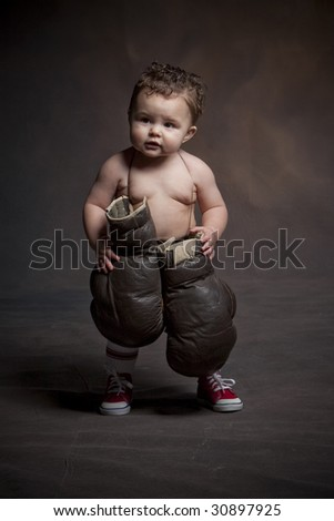 Little boxer with huge gloves - stock photo
