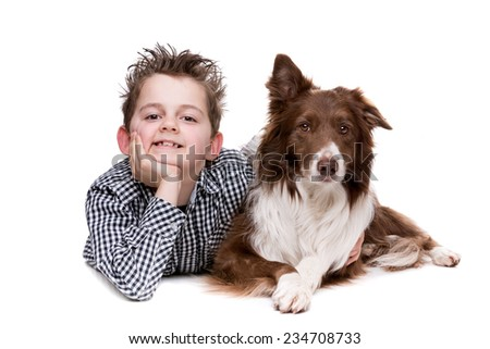 little boy and a border collie in front of a white background - stock photo