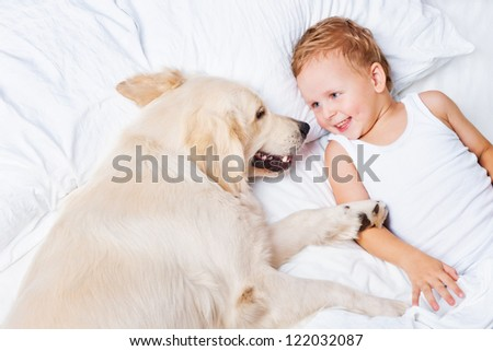Little boy and a dog in bed - stock photo