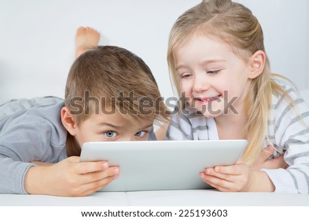 little boy and girl enjoying their tablet - stock photo