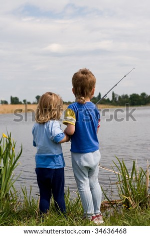 Little boy and girl fishing on the lake - stock photo