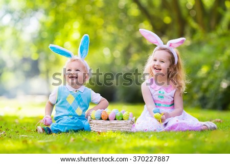 Little boy and girl having fun on Easter egg hunt. Kids in bunny ears and rabbit costume. Children with colorful eggs in a basket. Toddler kid and baby play outdoor on sunny spring day. Family holiday - stock photo