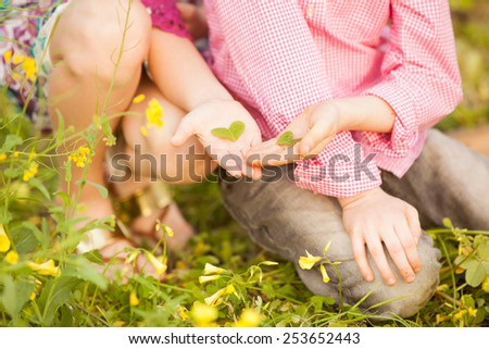 Little boy and girl holding in their hands green leaves in the shape of heart. - stock photo
