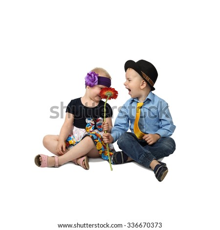 Little boy and girl in country style festive clothes sit on floor with flower in hands isolated on white background in square - stock photo