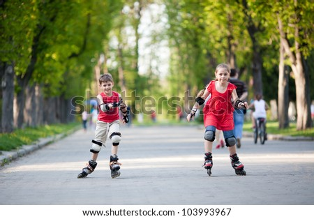 Little boy and girl on rollerblades competing - stock photo
