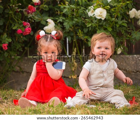 Little boy and girl playing with cellphones in the garden - stock photo