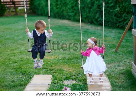 little boy and girl ride on a swing at the playground in the park. - stock photo