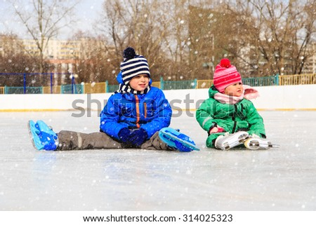 little boy and girl sitting on ice with skates, kids winter sport - stock photo