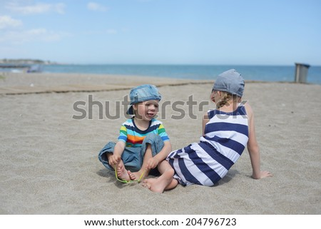 Little boy and girl sitting on the beach - stock photo